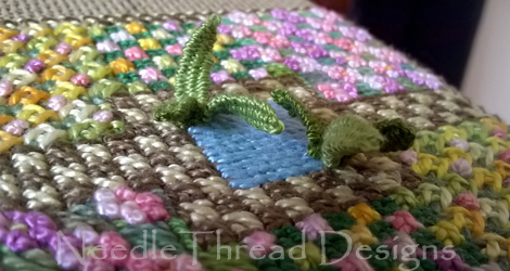 Canvas Work: close up of a garden design with canvas stitches and stumpwork leaves