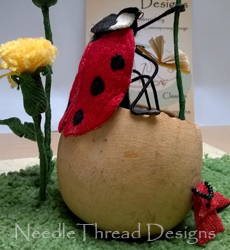 Stumpwork: raised embroidery ladybird cooling her feet in a seed pod