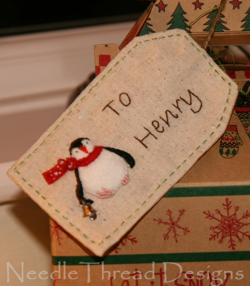 embroidered Christmas gift tag with a stumpwork (raised or padded) penguin
