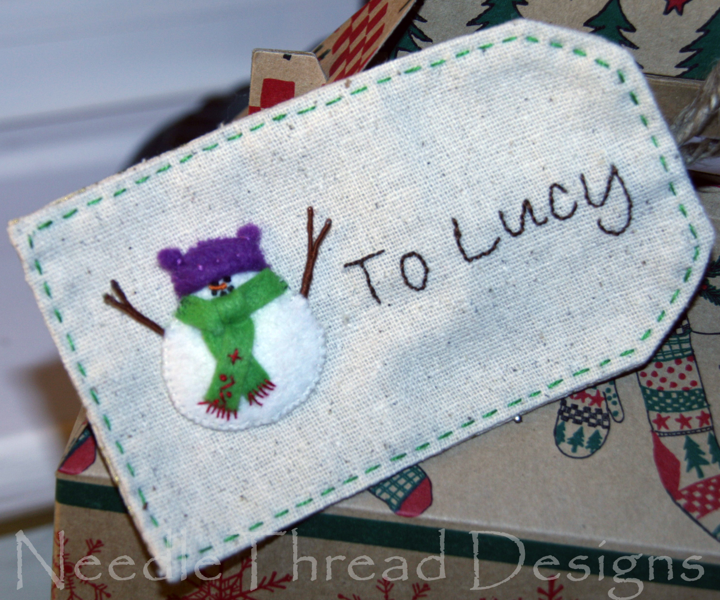embroidered Christmas gift tag with a stumpwork (raised or padded) snowman