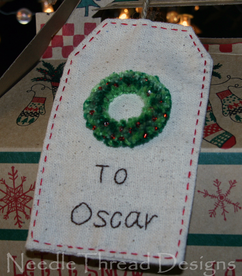 embroidered Christmas gift tag with a stumpwork (raised or padded) Christmas wreath