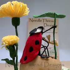 Close up of a stumpwork ladybird cooling her feet