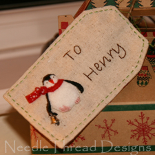 Close up of stumpwork christmas tag with Pip the Penguin